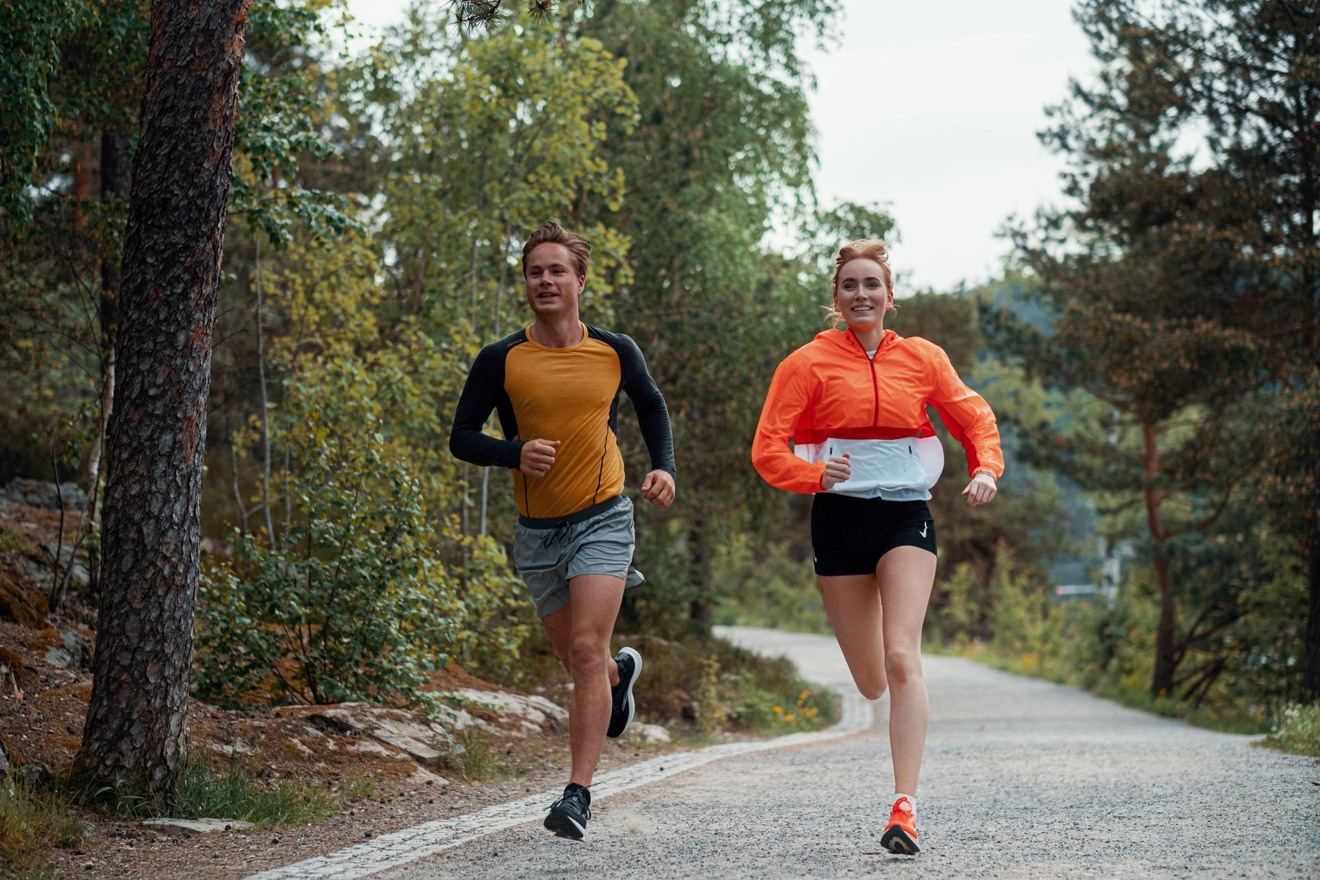 Ung mann og dame løper på grussti