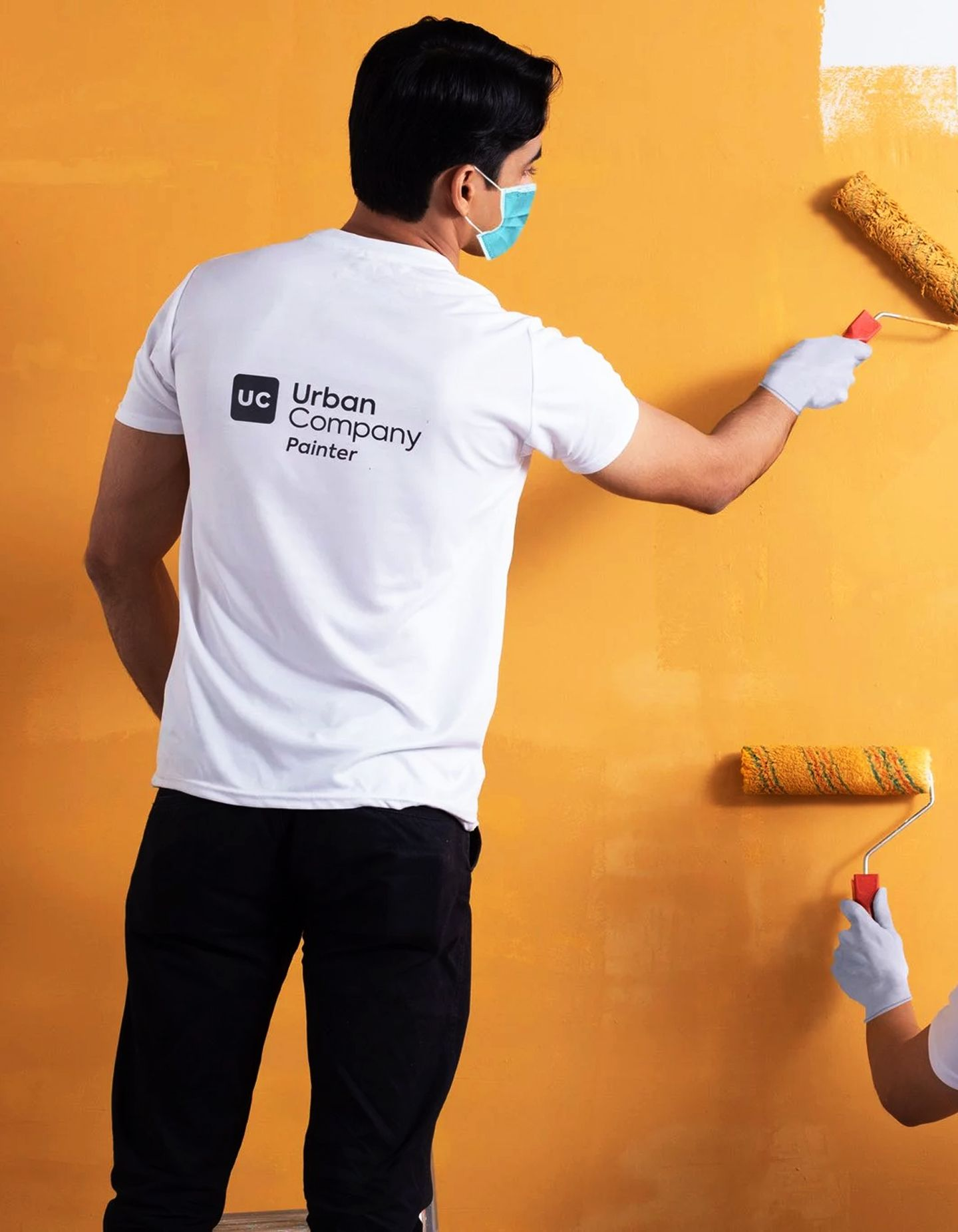 A two painters paint a wall orange for a job with Urban Company