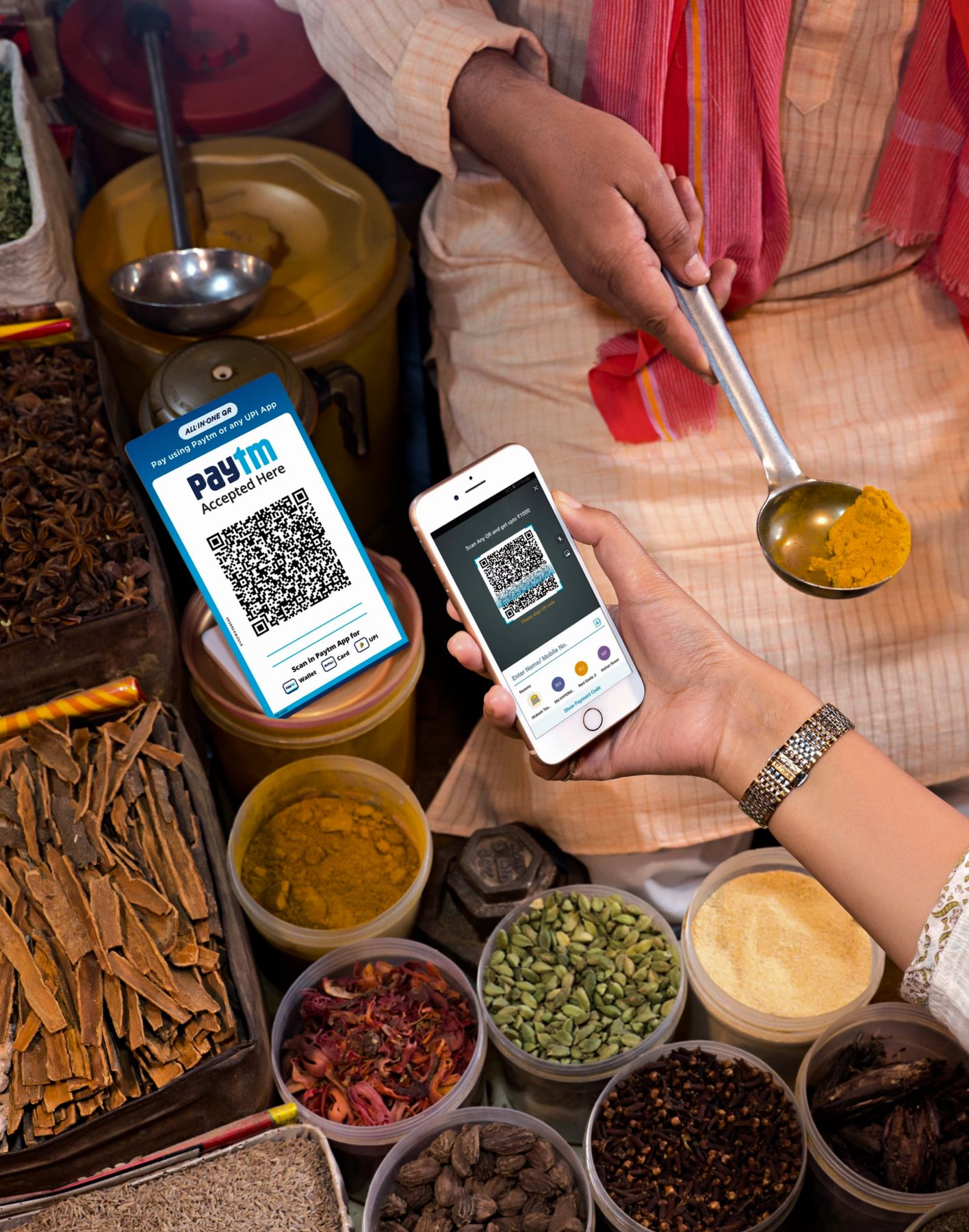 A customer using Paytm to pay for spices in a market