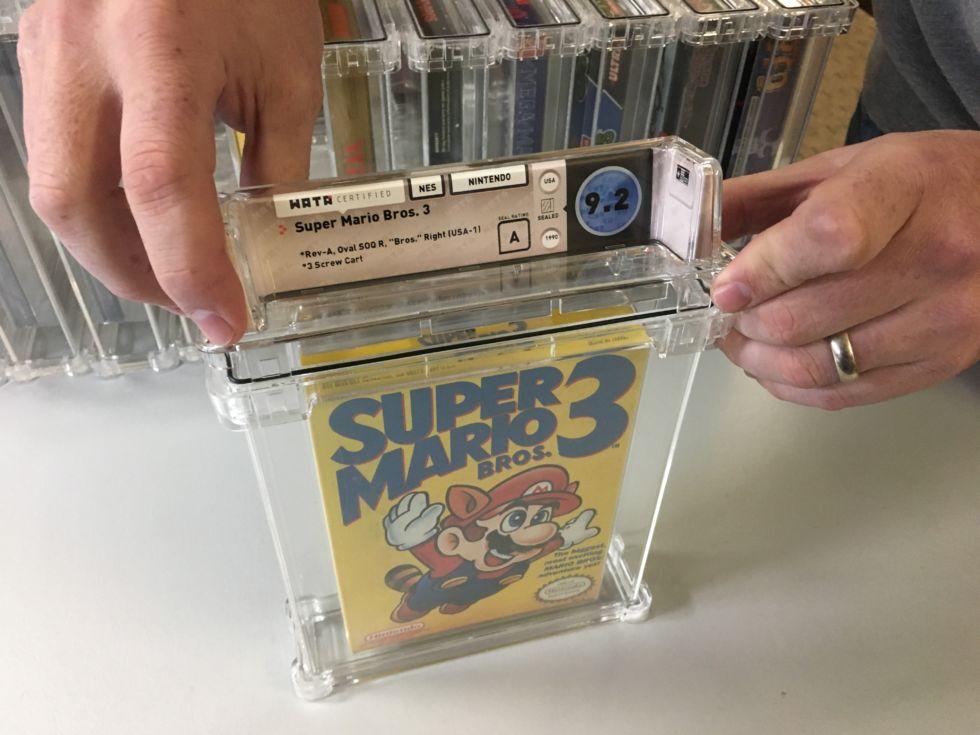 Специалист рейтинговой организации Wata Games после оценки состояния запечатанной упаковки с игрой помещает ее в пластиковый контейнер с краткой информацией об игре и баллами за состояние копии
