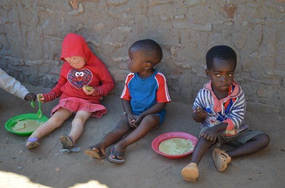 Children, one with albinism, eating porridge