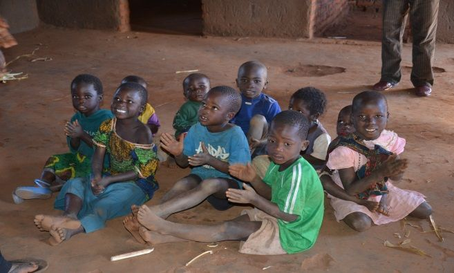 Children singing and clapping to a song at Chiweza II CBCC