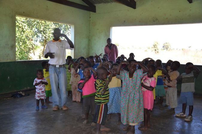 Caregiver teaching the children an action game at Namanyanga CBCC