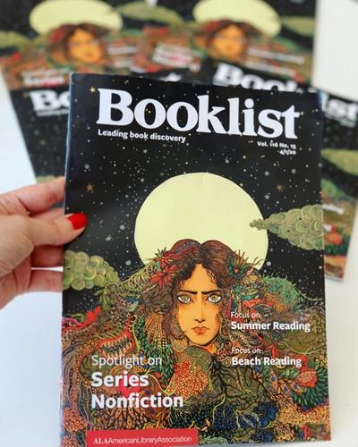 A hand holding the 4/1/2020 edition of Booklist, which features Lobizona as the cover image.