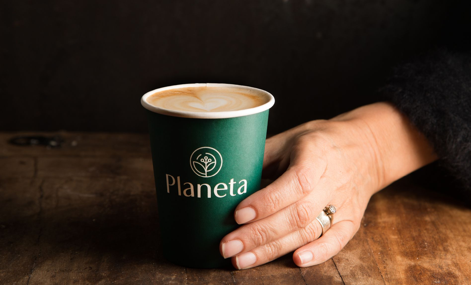 Hand holding a branded Planeta coffee cup
