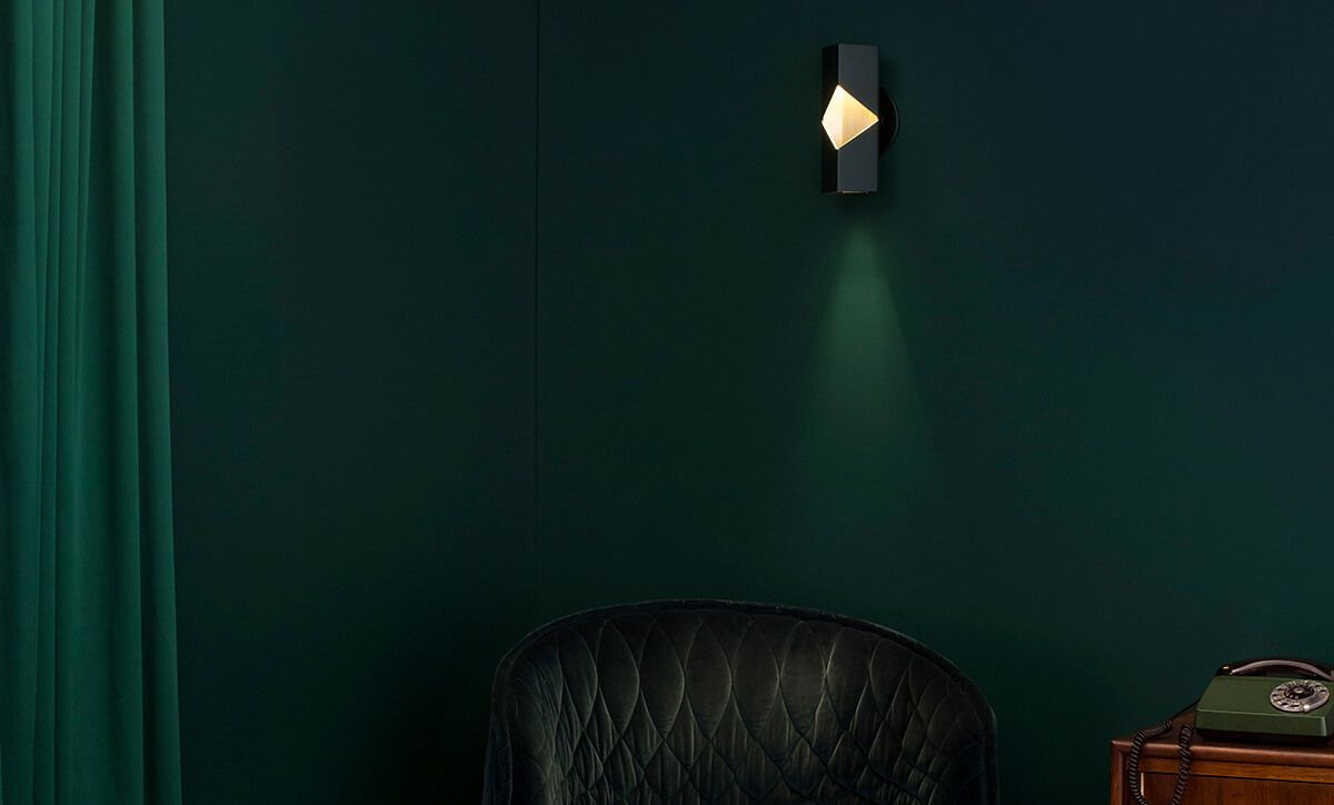 Matte black Notch sconce installed in a room with green walls