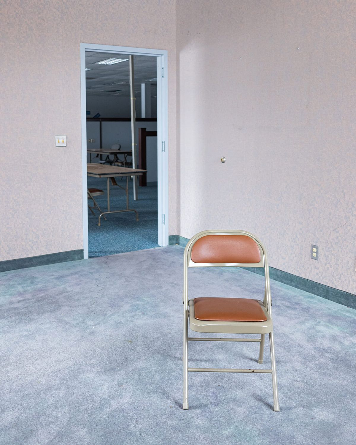 Views of the existing interior, carpeted floor, wall paper, and foldable office chairs