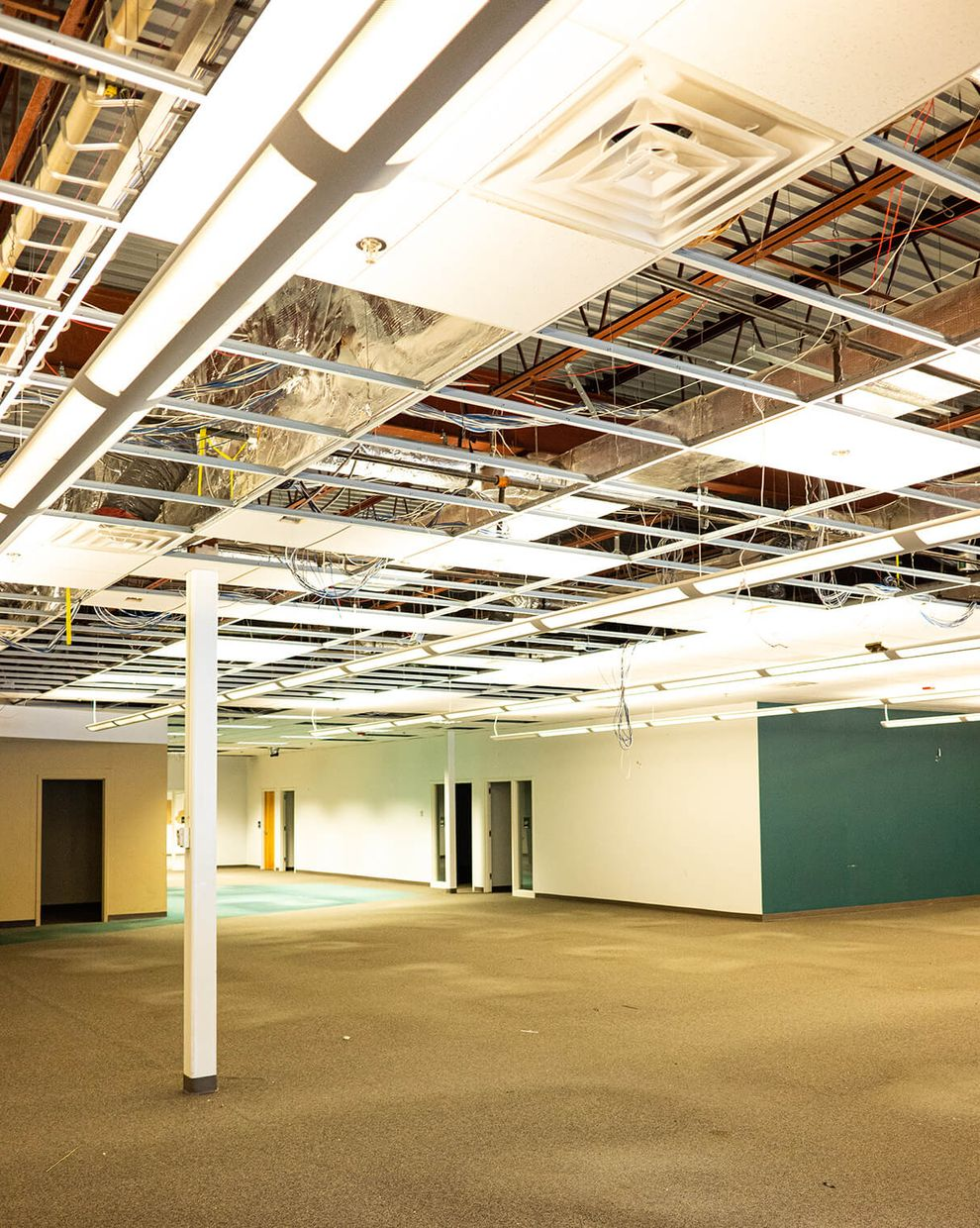 Missing ceiling panels reveal the 16 ft ceilings above