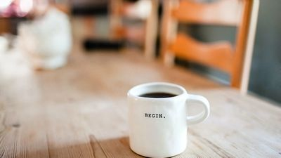 Coffee cup on a wooden table with the word BEGIN printed on the cup