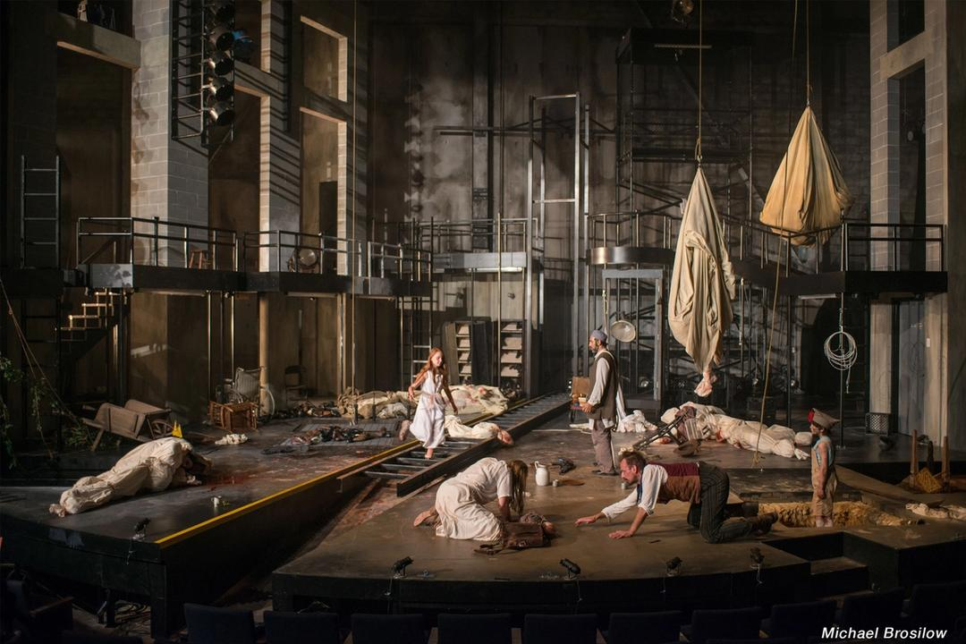A stage set up to look like the interior of a building, with three actors on the floor and two standing.