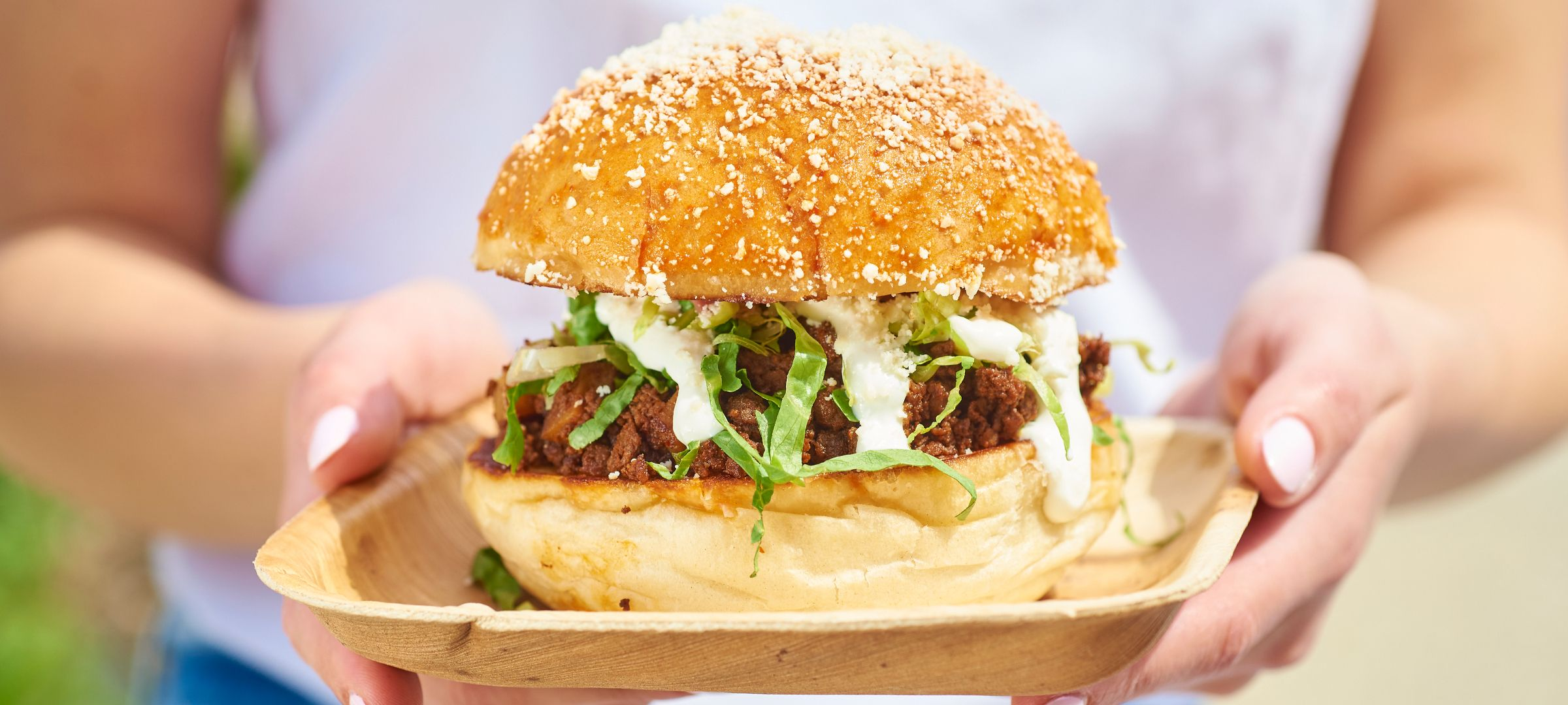 A view of someone holding a burger on a plate