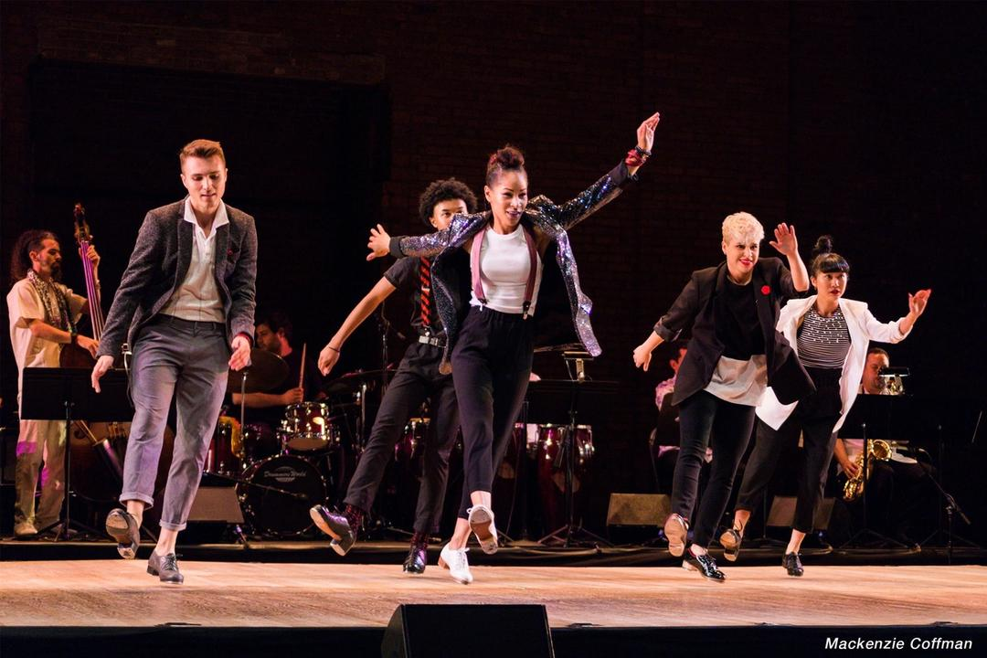 Three women and two men tap dancing on a stage, in front of a band.