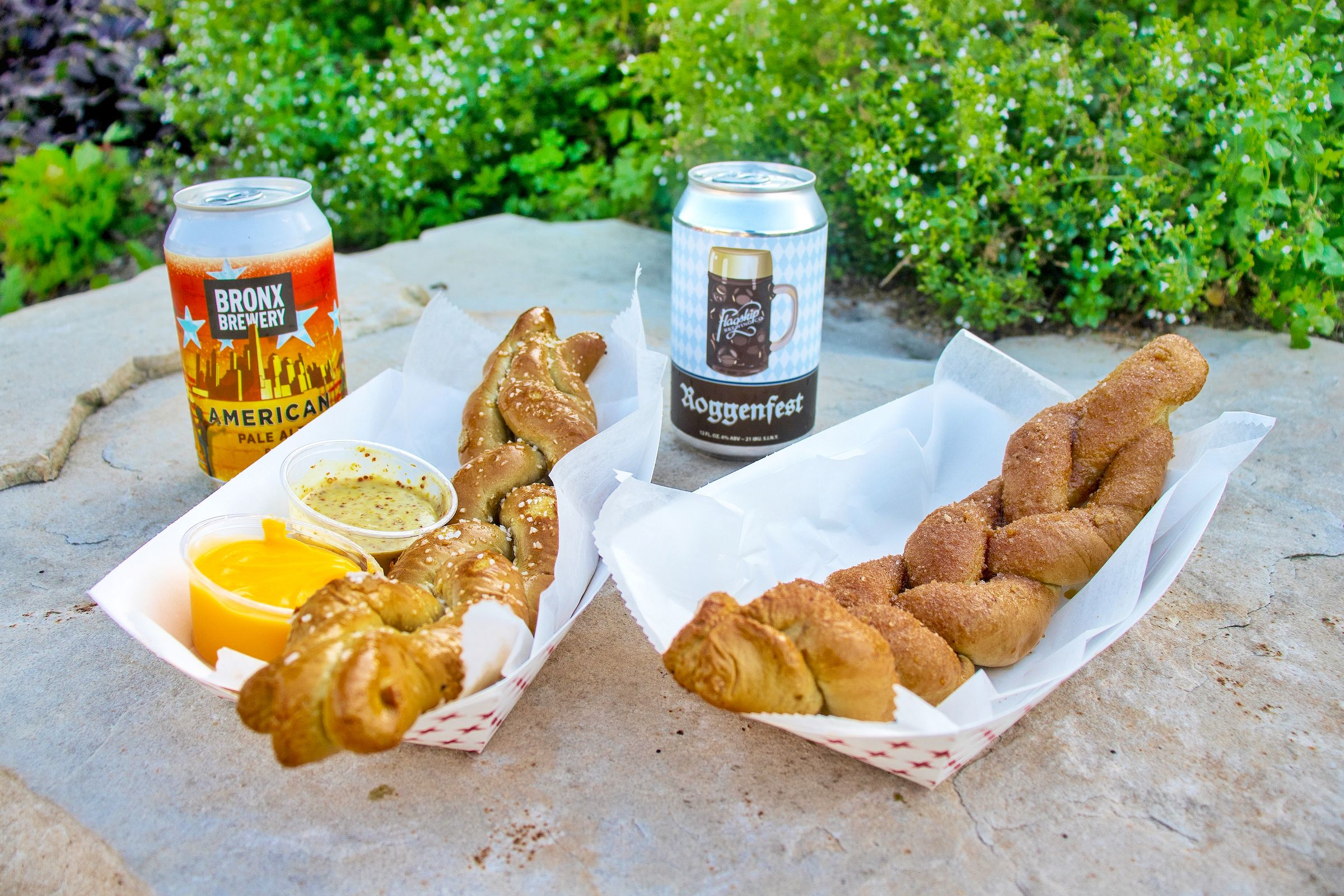 Two beer cans and one pretzel twist with salt and one pretzel twist with cinnamon sugar.