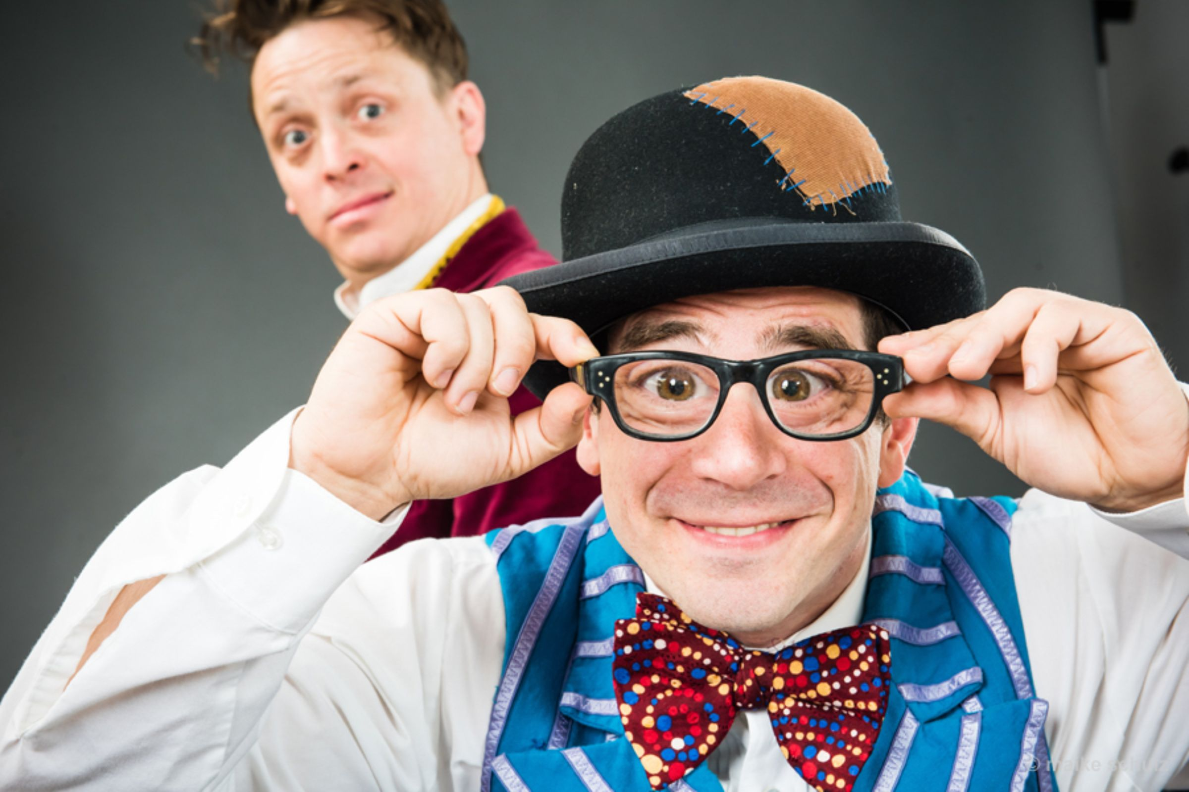 Man with glasses held to his face standing in foreground with another man in the background