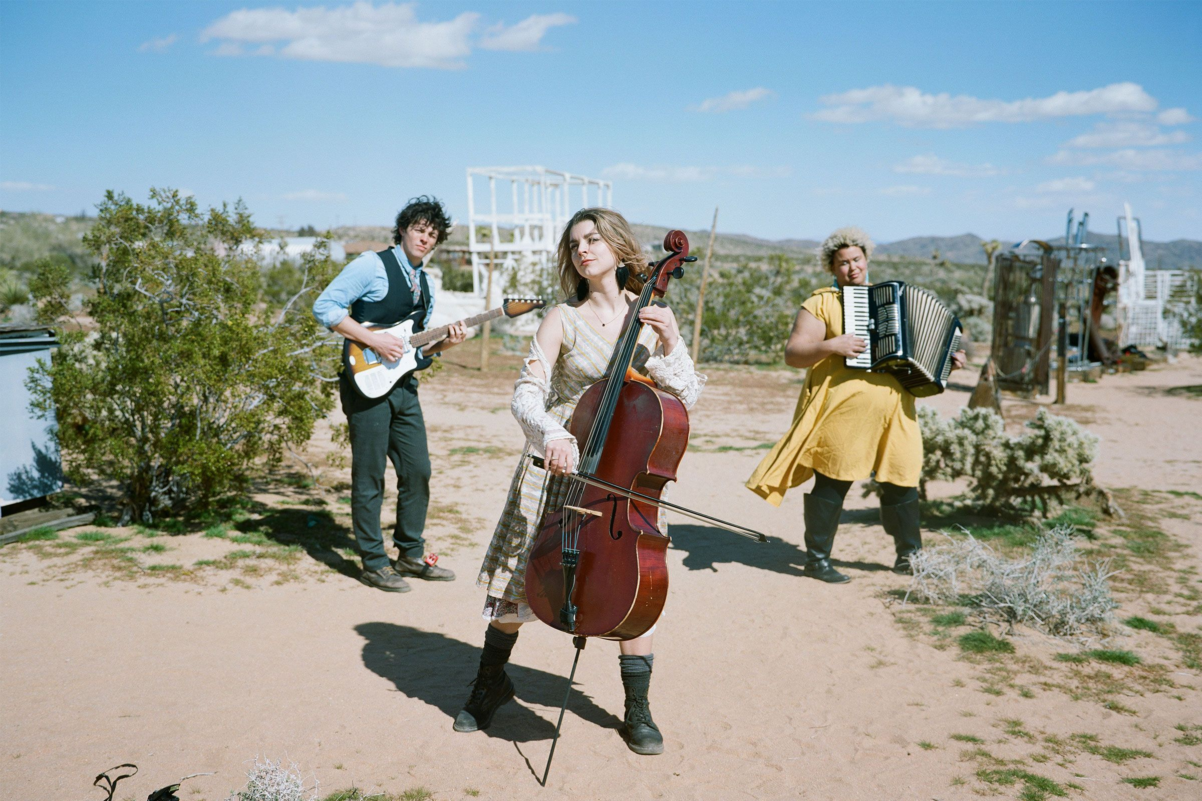 Three people standing in a desert holding instruments. Two people in the background are holing a guitar and accordion, and one woman in the foreground is holding a cello.