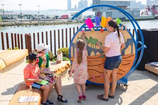 Children and adults engaging in an activity on our Art Cart
