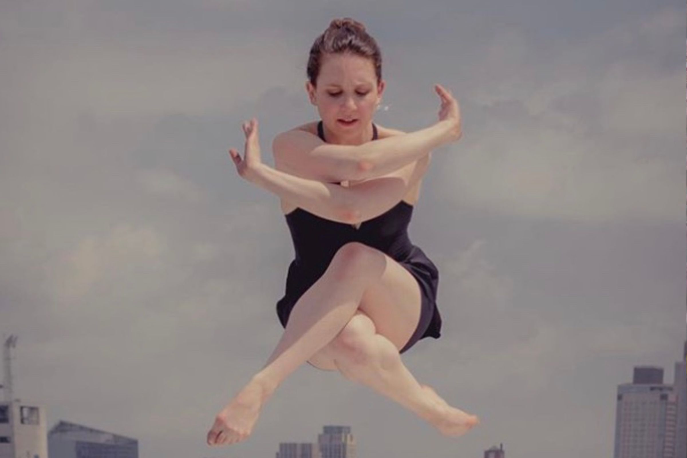 A woman hovering in the air with her arms and legs crossed