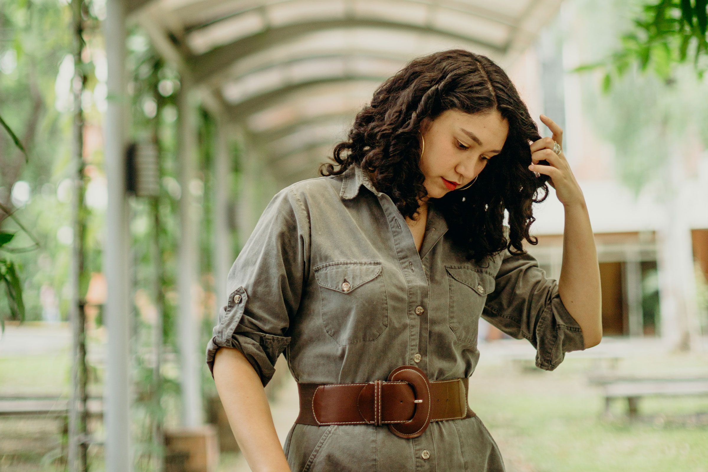 A woman dressed in an olive green button down shirt looking down