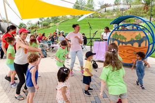 A group of children and adults dancing with people sitting and watching in the background
