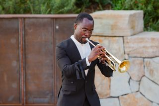 A man in a black suit playing the trumpet