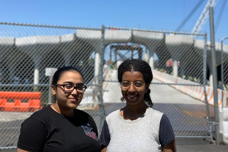 Two young women standing in front of the park's construction site.