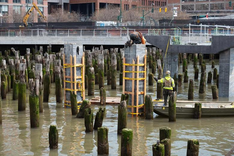 Two construction workers building out column supports on the water.