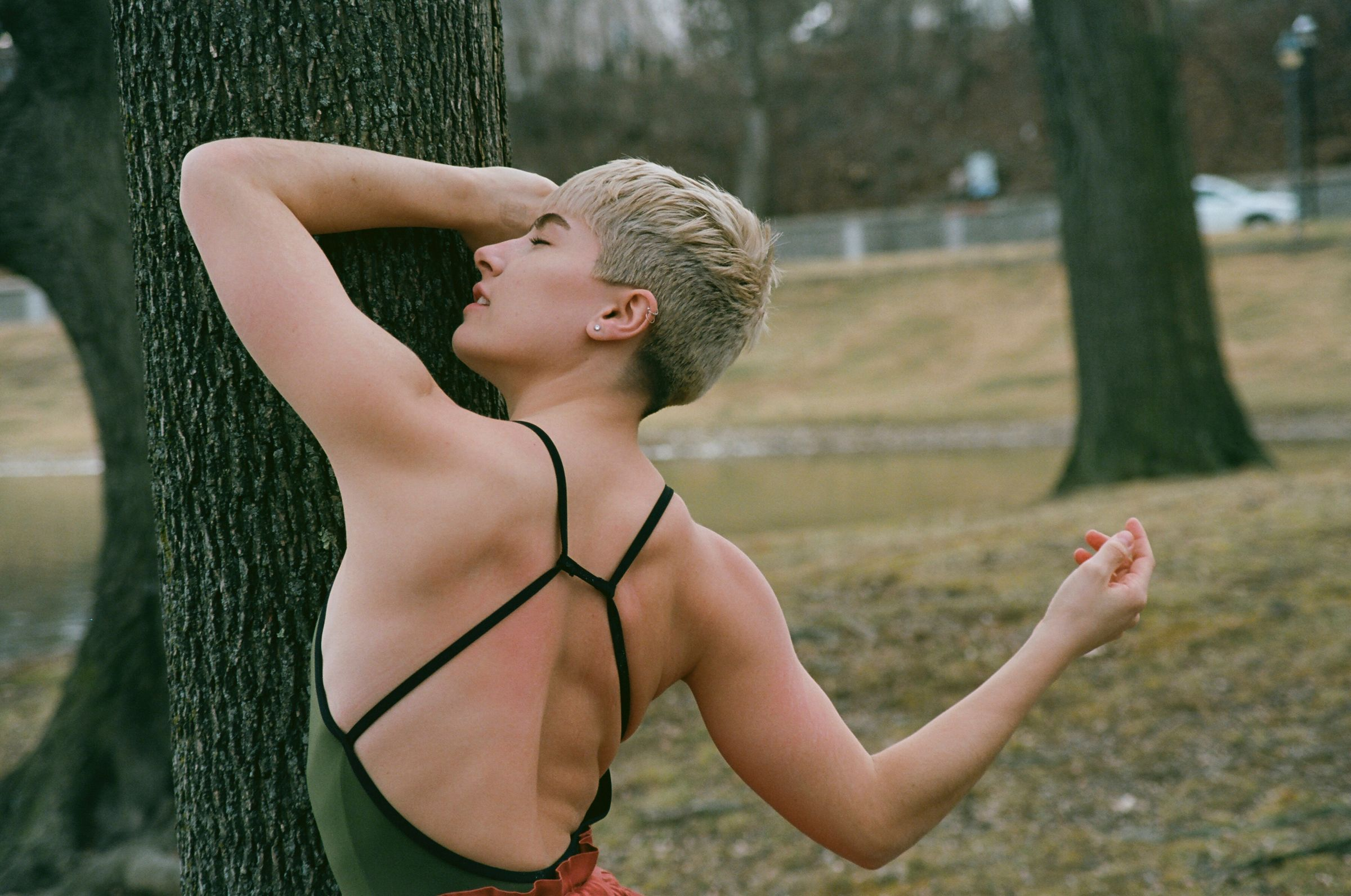 A woman dancing and swaying outside in front of a tree
