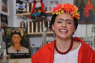 A woman dressed as Frida Kalho, in a white blouse, with a bright red shawl, wearing a ruby red beaded necklace and a bright red and yellow flower crown on her head, smiling
