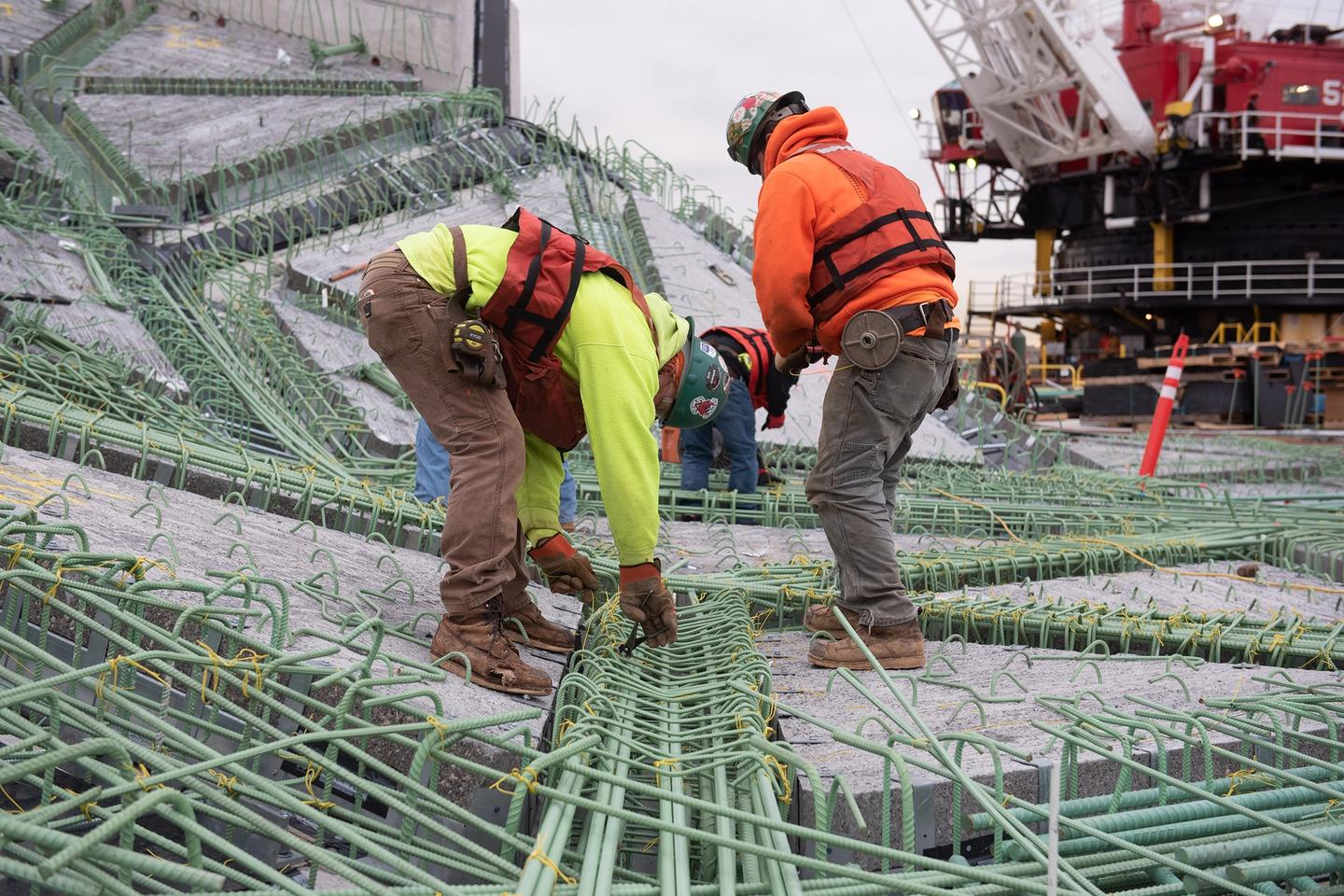 Construction workers securing rebar on the ground.