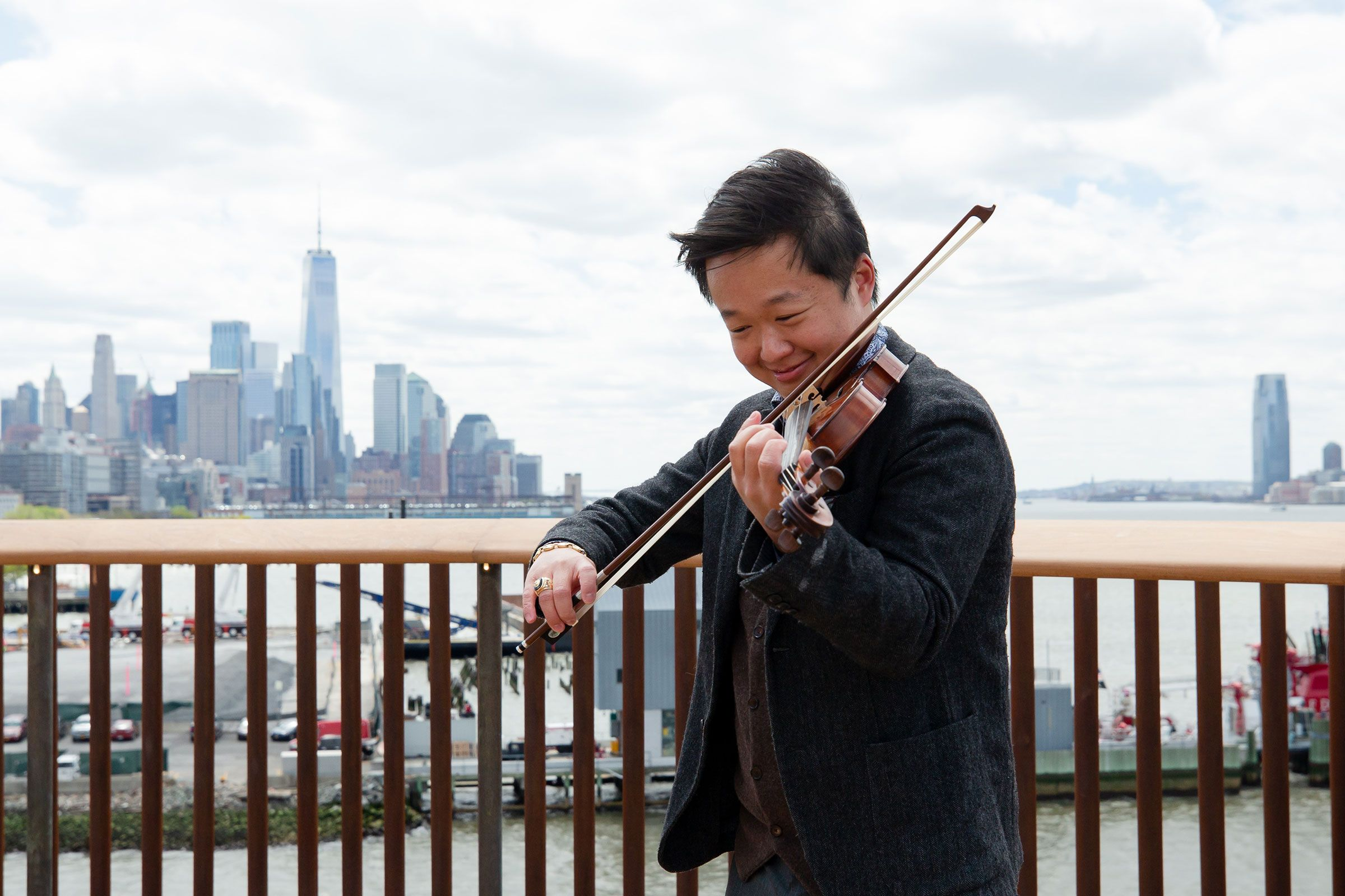 Man playing the violin with the city skyline in the background
