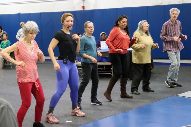 Senior citizens in a line dancing salsa.