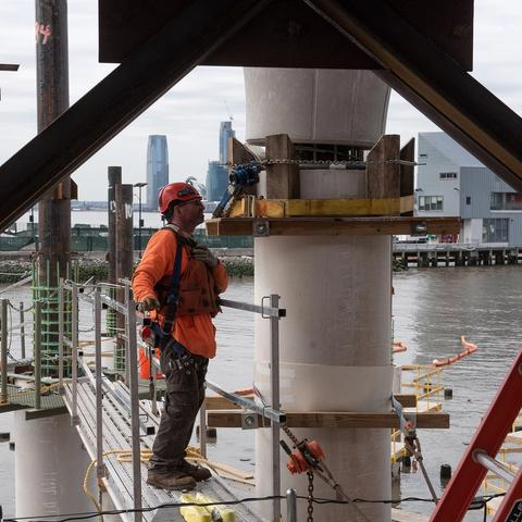 A construction worker checks one of the concrete pillars.