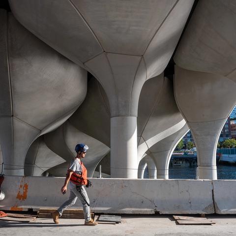 A construction worker walks under the concrete pots.