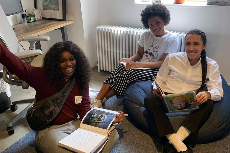 Two young women and one young man sitting on bean bag chairs, holding books and smiling.