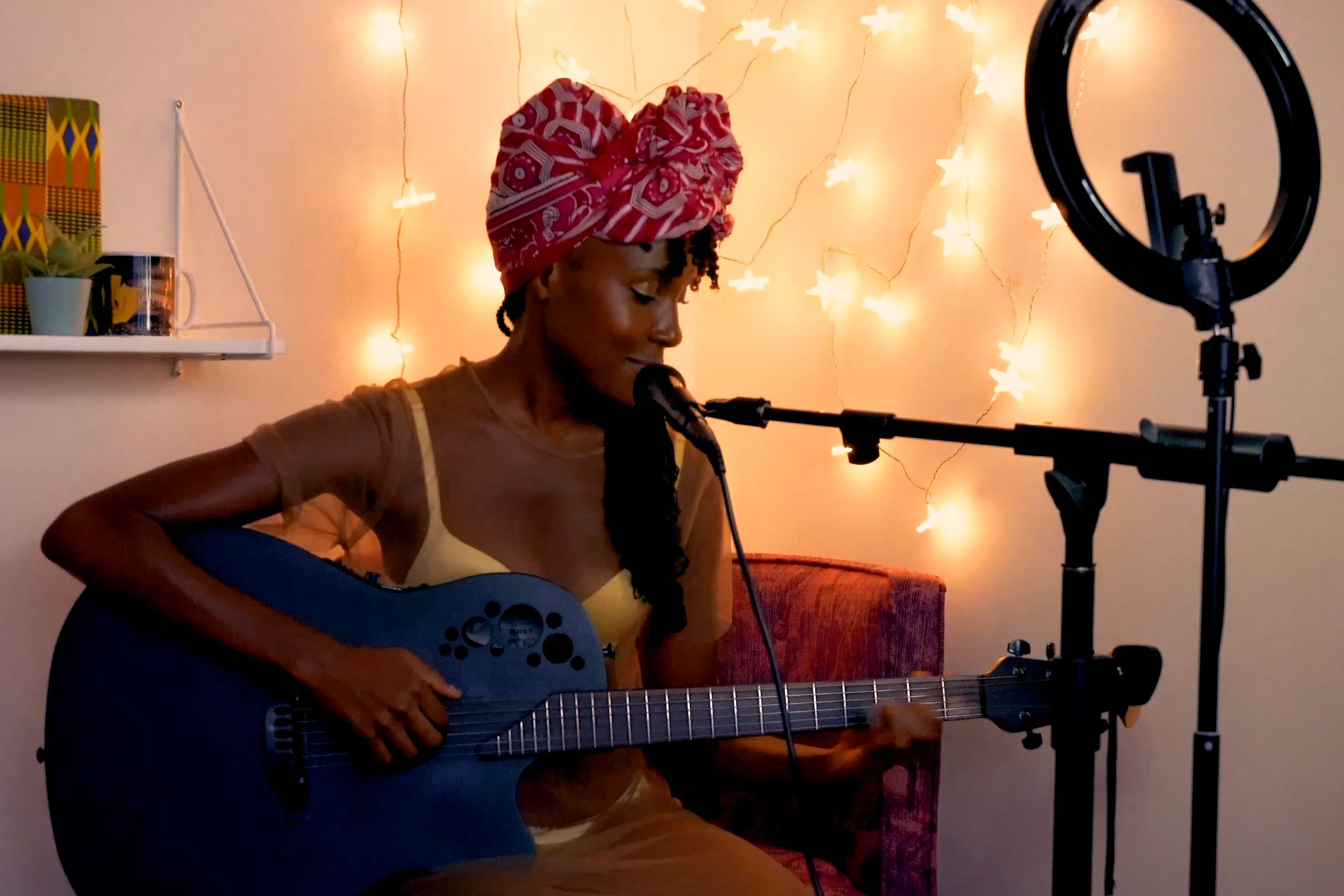 Woman sitting down, playing the guitar and singing