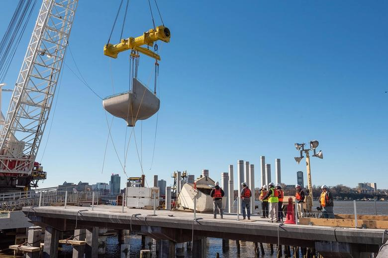 A crane lifting a concrete pot into place.