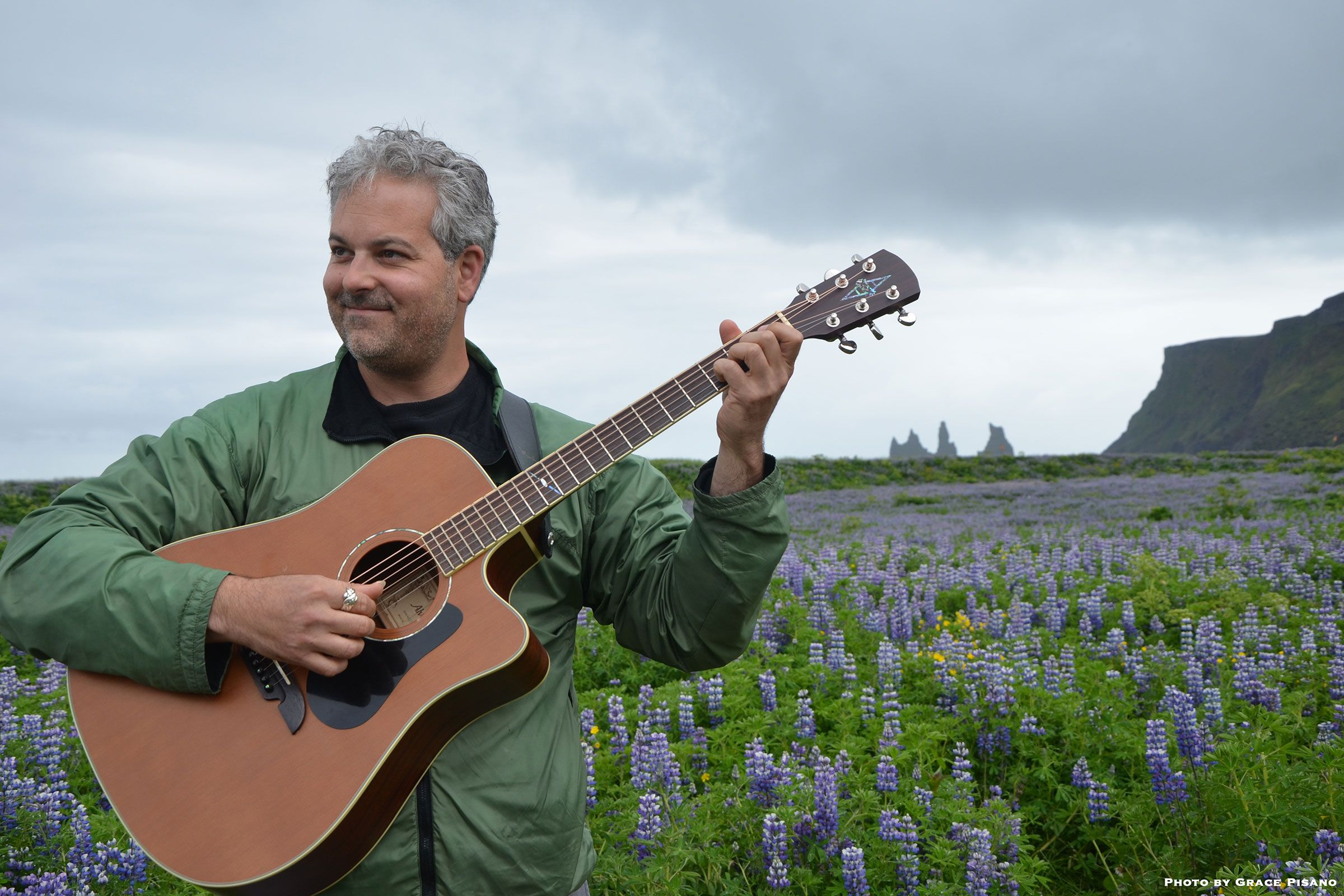 Man playing the guitar outside in a flower field