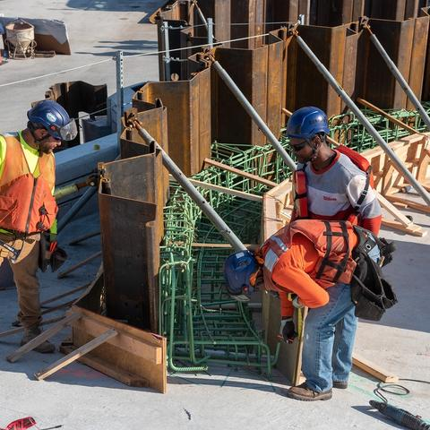 Three construction workers securing rebar in place.