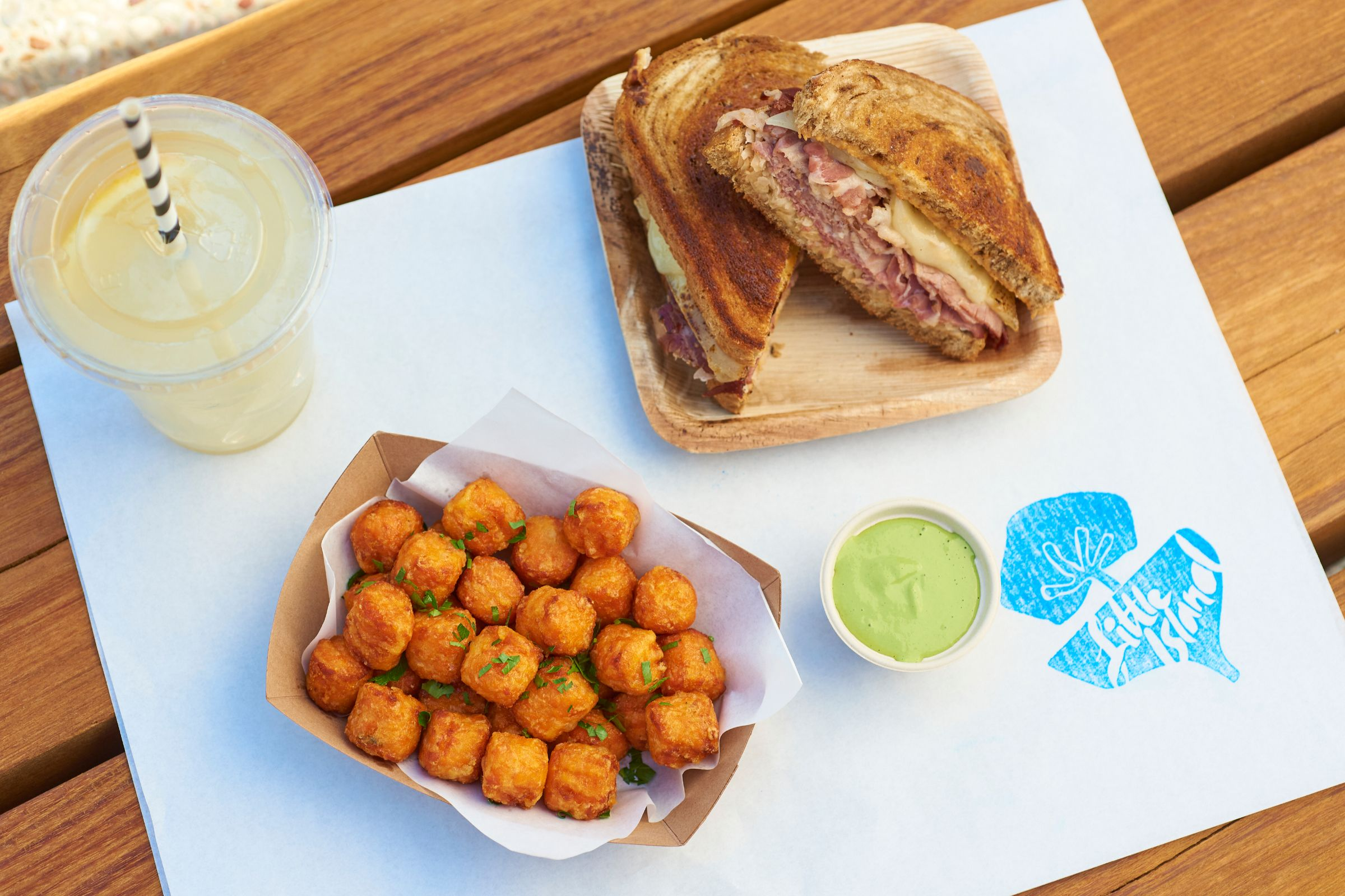 A drink, tater tots, and a sandwich on a table