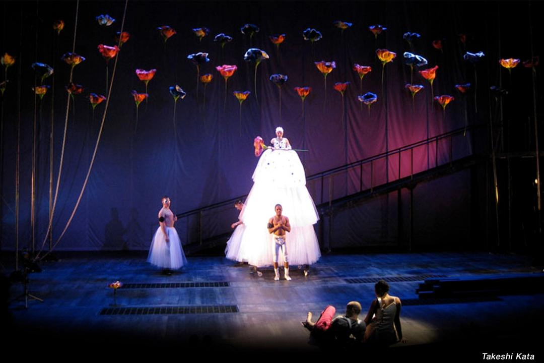 A theatrical production with large flowers suspended as part of the set design.