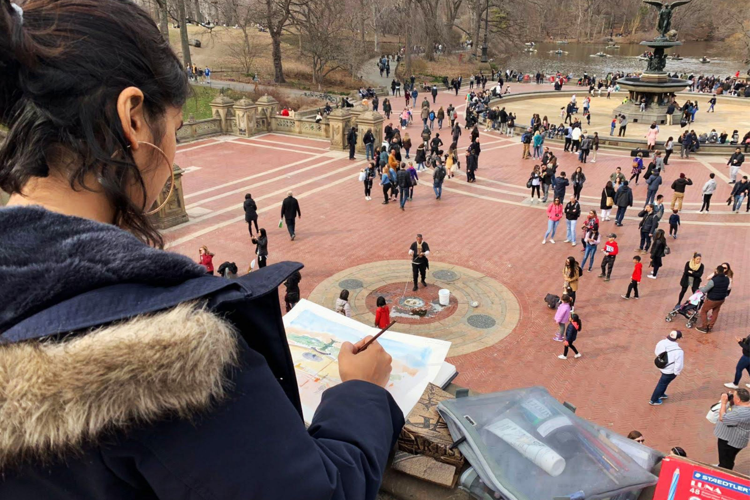 Woman drawing while looking over a railing at people and a fountain below