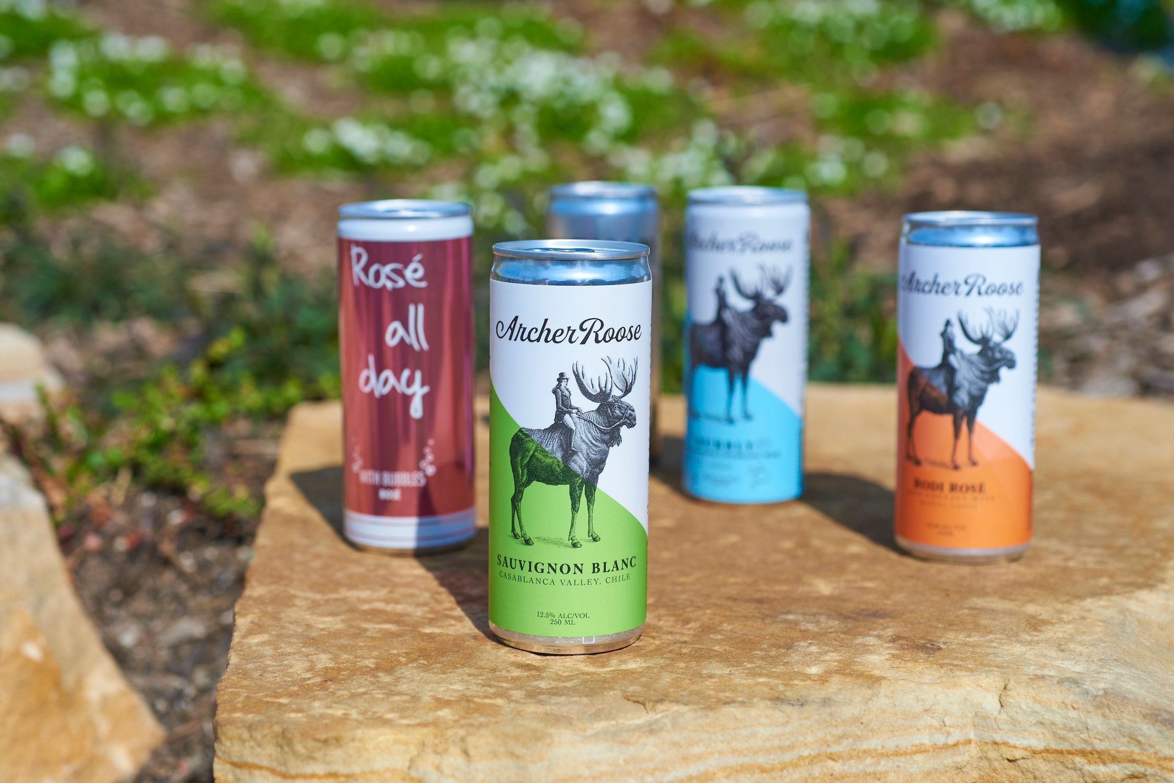 Different drinks in cans set on a rock
