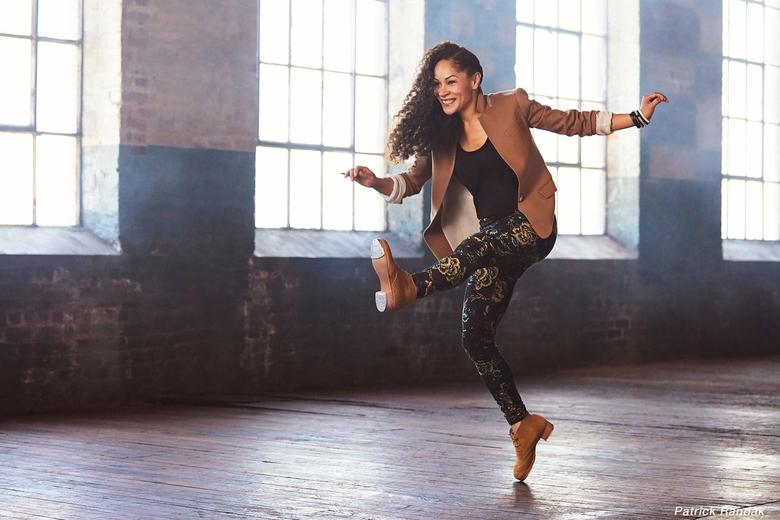 A woman mid-jump, tap dancing.