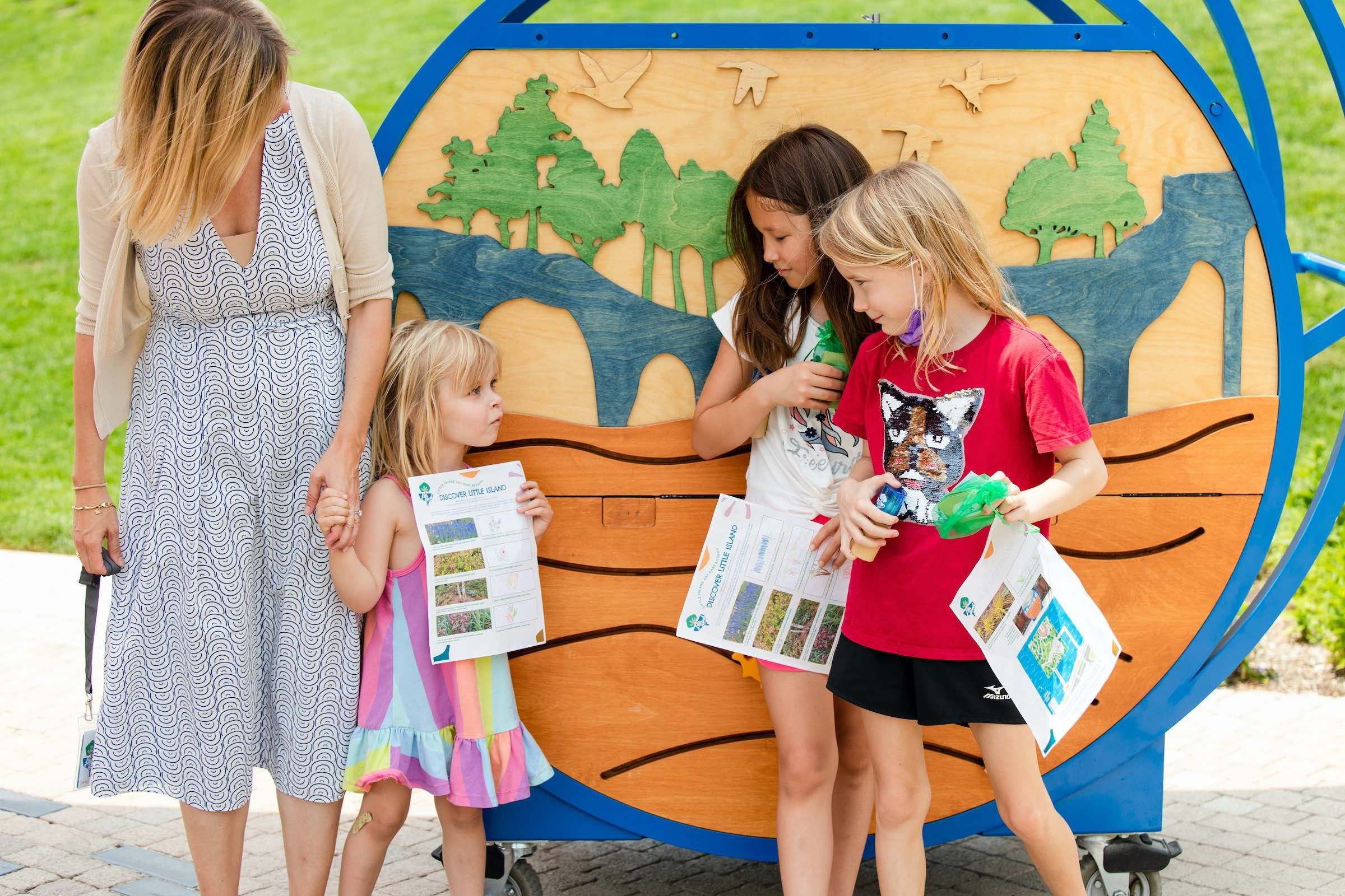 Three children and an adult standing in front of the Little Island Art Cart, holding Little Island activity sheets