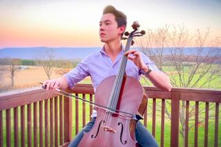 A man in a light purple shirt sitting outside at a wooden balcony playing a cello, with a field and mountains in the background