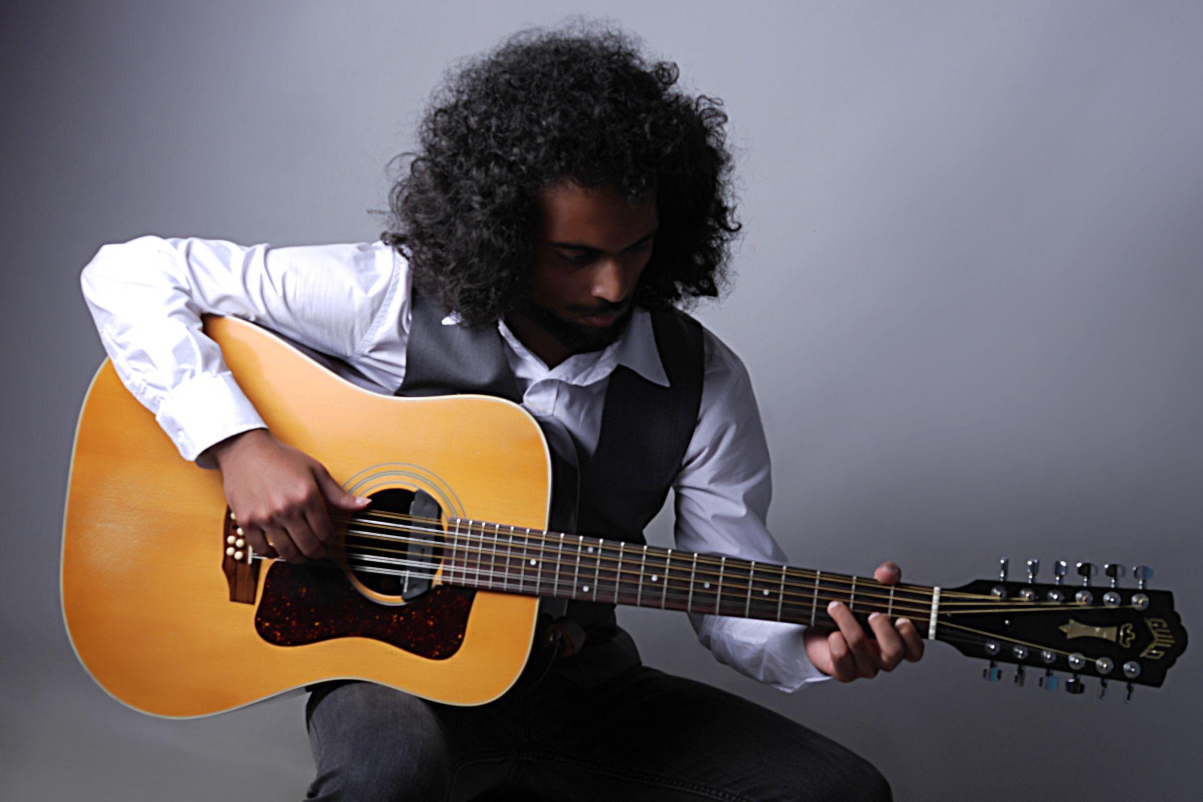 Sitting man holding a guitar