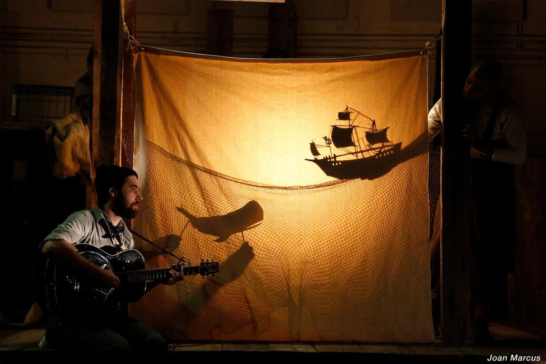 A man playing a guitar in front of a backlit curtain, where the shadow of a ship and a whale appears.