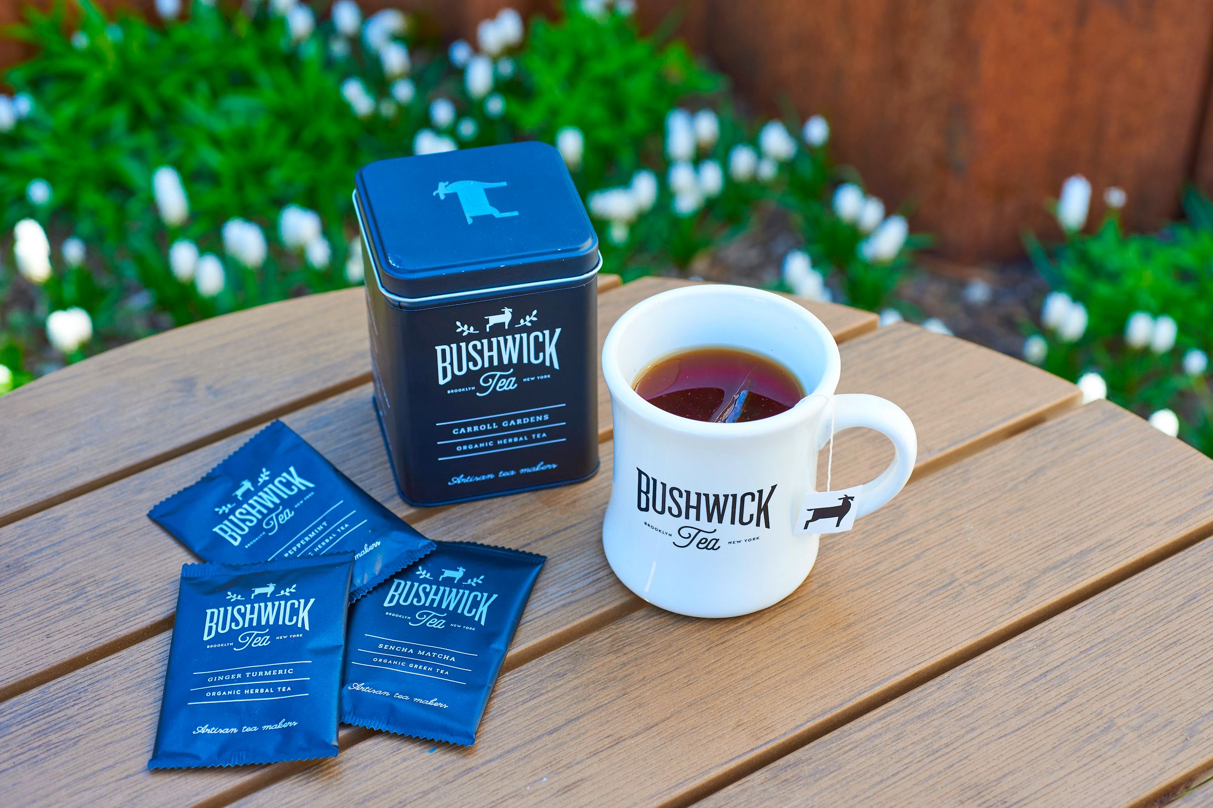 A blue canister sits on a wooden table next to blue tea bags and a white mug filled with tea