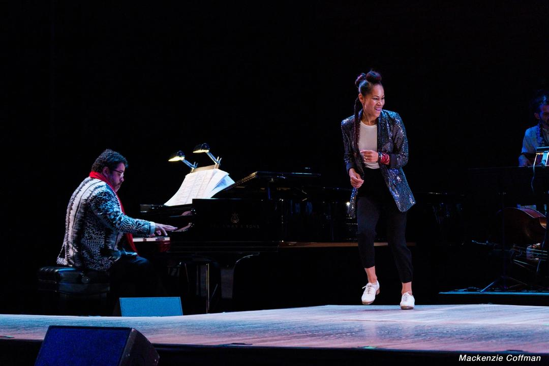 A woman tap dancing on stage, next to a man playing at a piano.