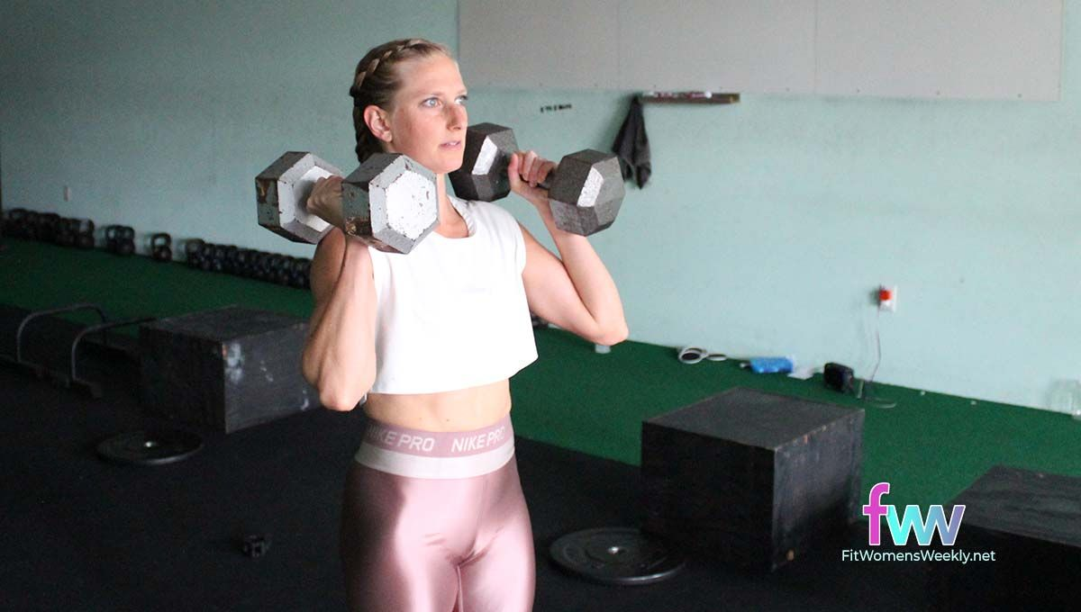 Standing with a dumbbell in each hand with the bell resting on the shoulders before a squat.